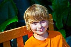 Retrato de un muchacho que se sienta en un banco Foto de archivo