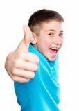 Retrato de un muchacho que señala el finger que muestra las emociones expresivas en un fondo blanco con una camisa azul Imagen de archivo