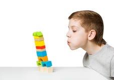 Retrato de un muchacho que sopla en la casa que cae hecha de bloques de madera Imagenes de archivo