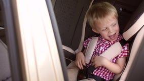 Retrato de un muchacho de risa alegre en un asiento de carro del ` s de los niños Cámara lenta almacen de metraje de vídeo