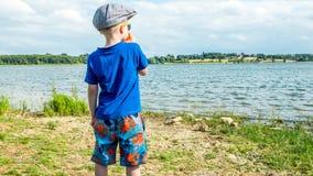 Retrato de un muchacho rubio en fondo del lago Imágenes de archivo libres de regalías
