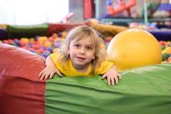 Retrato de un muchacho rubio en una camiseta amarilla Las sonrisas y los juegos del niño en la sala de juegos de los niños Piscin foto de archivo