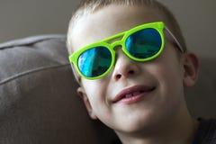 Retrato de un muchacho sonriente bonito del niño en gafas de sol Imagen de archivo libre de regalías