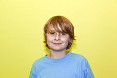 Retrato de un muchacho sonriente con el pelo rubio largo Imagen de archivo