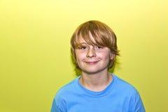 Retrato de un muchacho sonriente con el pelo rubio largo Fotografía de archivo