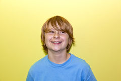 Retrato de un muchacho sonriente con el pelo rubio largo Foto de archivo libre de regalías