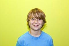 Retrato de un muchacho sonriente con el pelo rubio largo Imagen de archivo libre de regalías