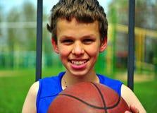 Retrato de un muchacho sonriente con un baloncesto Fotografía de archivo