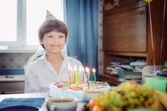 Retrato de un muchacho sonriente en la tabla en torta delantera con las velas imágenes de archivo libres de regalías