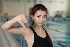Retrato de un nadador de sexo femenino del ajuste que gesticula los pulgares abajo por la piscina en el centro del ocio Foto de archivo