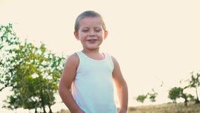 Retrato de un niño activo alegre en un fondo de la naturaleza Niño pequeño que sonríe mirando la cámara Niñez feliz almacen de video
