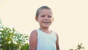 Retrato de un niño activo alegre en un fondo de la naturaleza Niño pequeño que sonríe mirando la cámara Niñez feliz metrajes