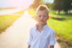 Retrato de un niño agradable en el camino en el día soleado Fotografía de archivo