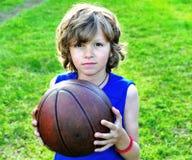 Retrato de un niño con un baloncesto en hierba Fotos de archivo
