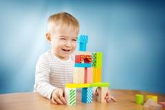 Retrato de un niño de dos años que se sienta en la tabla Fotos de archivo libres de regalías