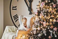 Retrato de un niño en el árbol de navidad grande y los carillones de Fotos de archivo