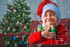 Retrato de un niño feliz con un regalo en el fondo de un árbol de navidad fotografía de archivo libre de regalías