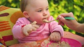 Retrato de un niño lindo y divertido, que se alimenta las gachas de avena con una cuchara metrajes