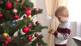 Retrato de un niño pequeño cerca de un árbol de navidad metrajes