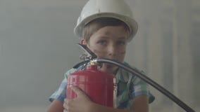 Retrato de un niño pequeño en un casco protector blanco con un extintor que mira la cámara en un fondo de almacen de metraje de vídeo