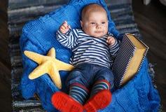 Retrato de un niño pequeño lindo en un chaleco rayado y botas fotos de archivo libres de regalías