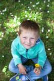 Retrato de un niño pequeño lindo que se sienta en la hierba Imágenes de archivo libres de regalías