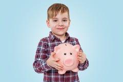 Retrato de un niño pequeño sonriente que sostiene la caja de dinero guarra Foto de archivo