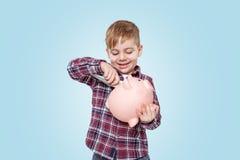 Retrato de un niño pequeño sonriente que sostiene la caja de dinero guarra Imágenes de archivo libres de regalías
