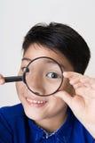 Retrato de un niño asiático joven que mira con un gla que magnifica Imagen de archivo