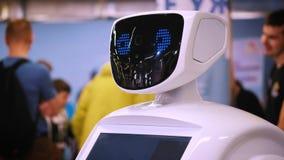Retrato de un nuevo robot blanco moderno El robot da vuelta a su cabeza, mira en la cámara Exposición de robots y alto