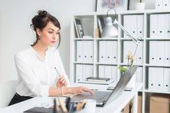 Retrato de un oficinista de sexo femenino joven que se sienta en su lugar de trabajo en la oficina, el mecanografiar, mirando en  Imagen de archivo libre de regalías