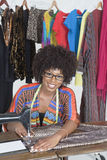 Retrato de un paño de costura del sastre de sexo femenino afroamericano en la máquina de coser Fotografía de archivo