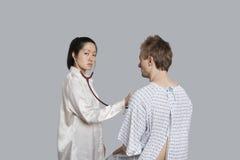 Retrato de un paciente masculino de examen del doctor de sexo femenino joven Foto de archivo libre de regalías