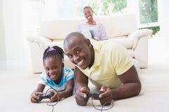 Retrato de un padre sonriente feliz que juega con su hija en los videojuegos Imagenes de archivo