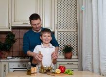 Retrato de un padre y de su hijo que preparan una ensalada en la cocina fotos de archivo