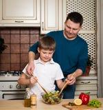 Retrato de un padre y de su hijo que preparan una ensalada en la cocina imagenes de archivo