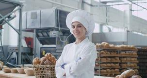 Retrato de un panadero hermoso grande sonriente de la mujer en un uniforme elegante que ella que miraba derecho a la cámara ha cr almacen de metraje de vídeo