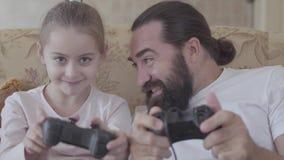 Retrato de un papá barbudo y de una pequeña hija linda que juegan a los videojuegos en la consola del juego que se sienta en el s almacen de video
