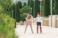 Retrato de un par adolescente encantador que patina sobre ruedas junto Fotos de archivo