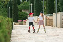 Retrato de un par adolescente encantador que patina sobre ruedas junto Imagenes de archivo