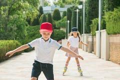Retrato de un par adolescente encantador que patina sobre ruedas junto Imagen de archivo libre de regalías