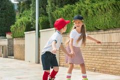 Retrato de un par adolescente encantador que patina sobre ruedas junto Fotografía de archivo