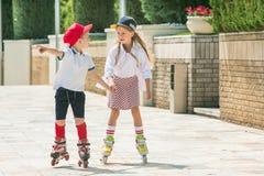 Retrato de un par adolescente encantador que patina sobre ruedas junto Fotos de archivo libres de regalías