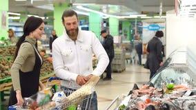 Retrato de un par bonito que elige pescados en supermercado Junte los pescados de compra almacen de video