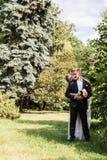 Retrato de un par del recién casado que se coloca de abarcamiento Imagenes de archivo