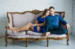 Retrato de un par elegante de moda que se sienta así como pies desnudos en el sofá en la sala de estar, abrazando, sonriendo, foto de archivo