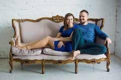 Retrato de un par elegante de moda que se sienta así como pies desnudos en el sofá en la sala de estar, abrazando, sonriendo, imagenes de archivo