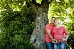 Retrato de un par embarazada feliz en vaqueros y camisetas rosadas Fotografía de archivo