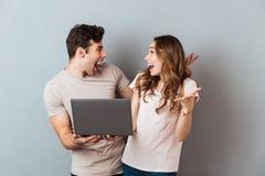 Retrato de un par feliz alegre que sostiene el ordenador portátil Foto de archivo libre de regalías