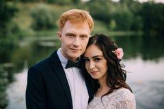Retrato de un par feliz del recién casado en la orilla del río Imagenes de archivo